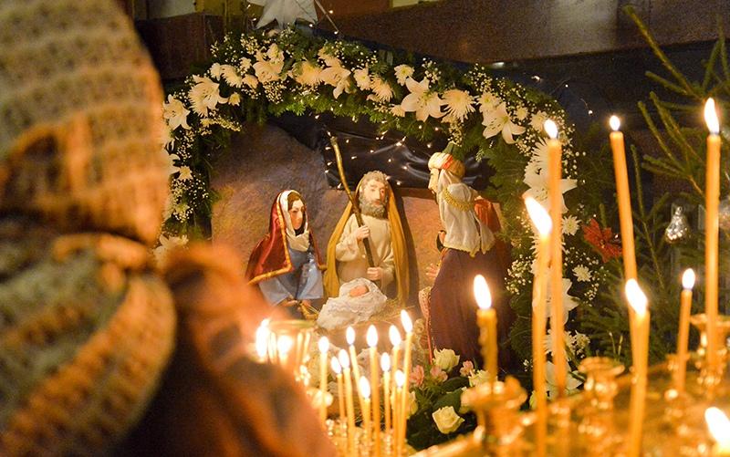 Женщина возле Рождественского вертепа