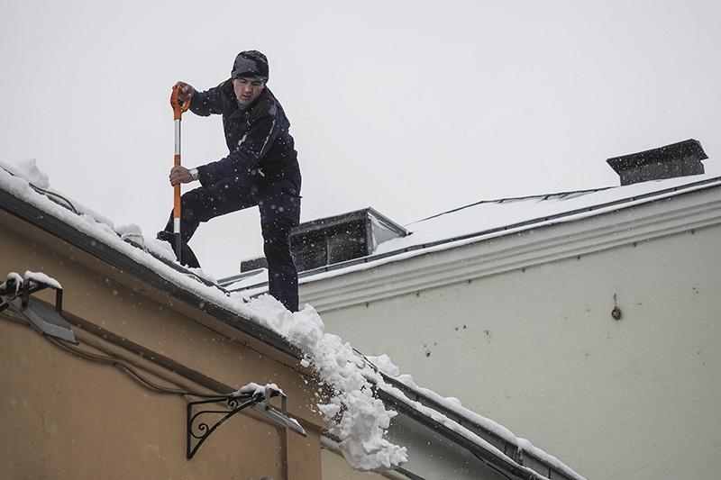 Сотрудник коммунальной службы убирает снег с крыши дома