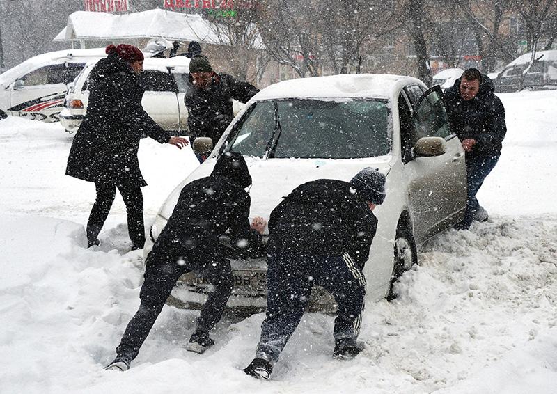 Люди выталкивают машину из сугроба