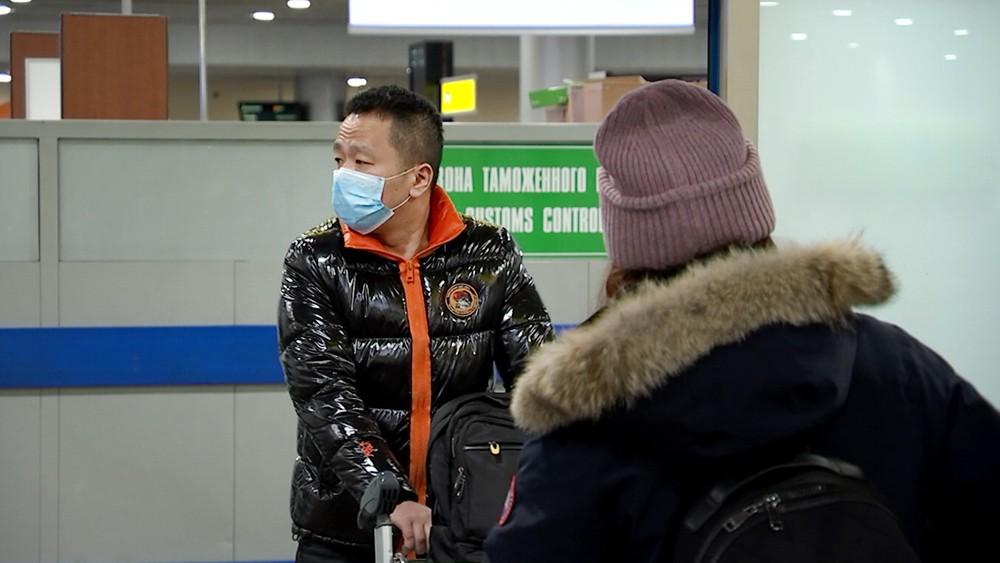 Пассажиры из Китая в медицинских масках в аэропорту