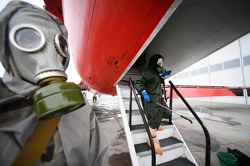 Специалисты в костюмах биозащиты выходят из самолета
