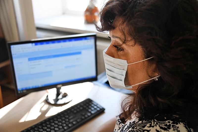 Женщина в медицинской маске у компьютера
