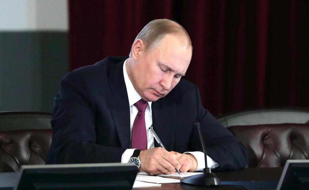 Владимир Путин подписывает документ