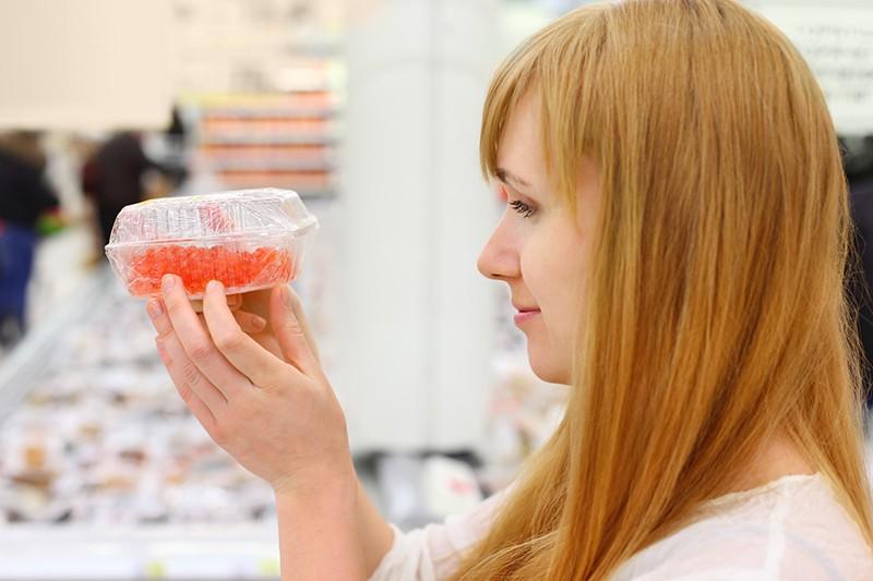 Девушка покупает икру