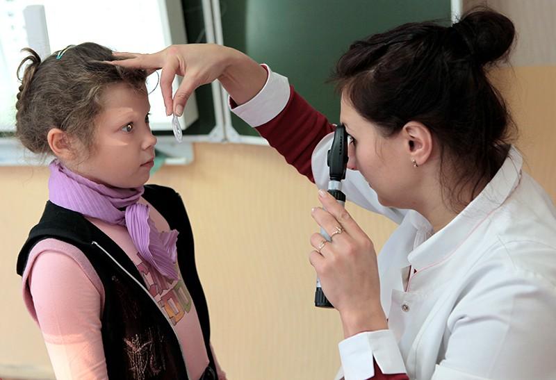 Окулист проверяет школьницу