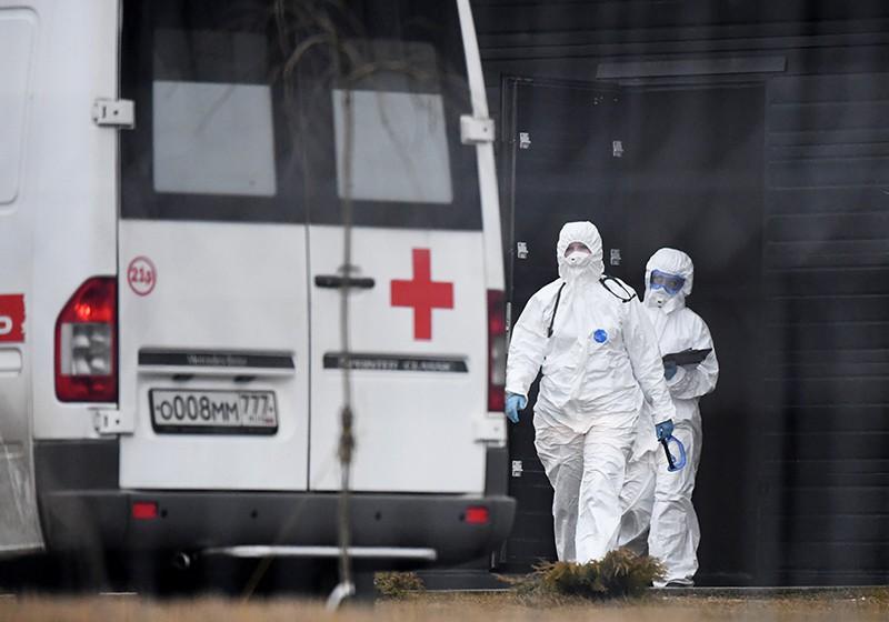 Сотрудники скорой помощи в защитных костюмах