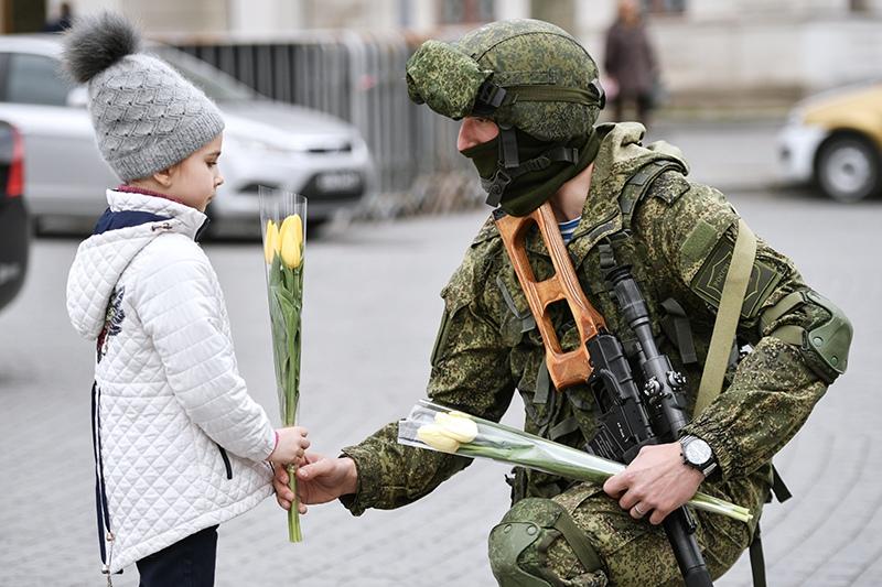 Военнослужащий Черноморского флота поздравляет девочку в преддверии праздника