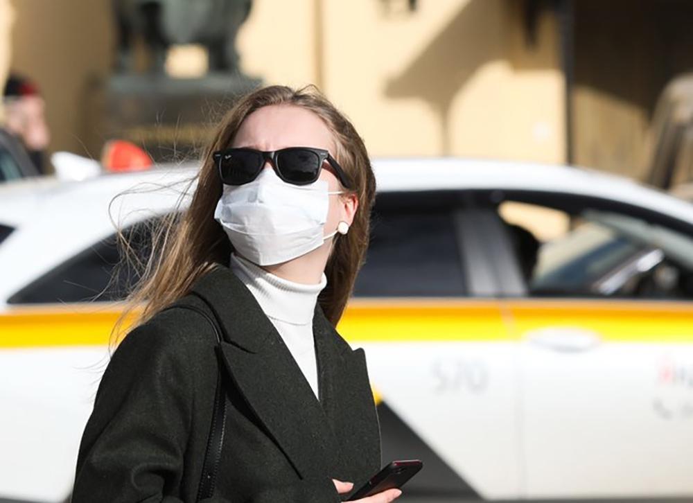 Девушка в маске на фоне такси