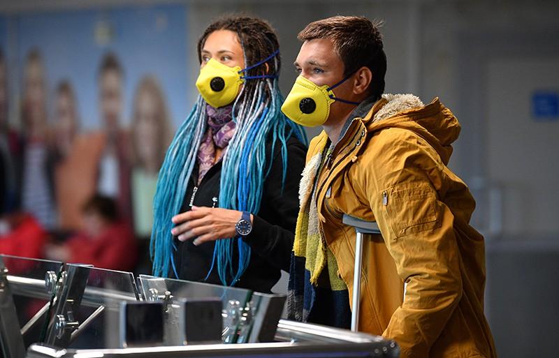 Пассажиры в защитных масках в аэропорту