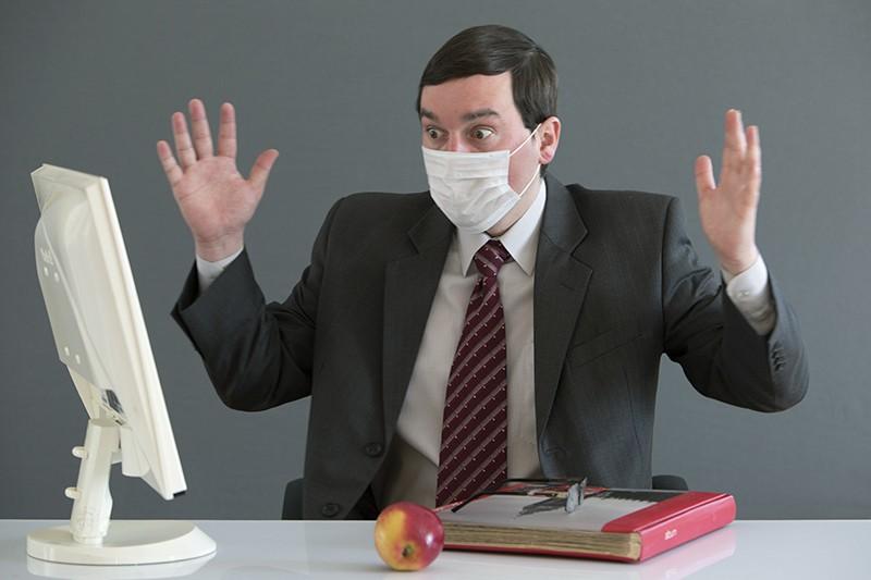 Мужчина в медицинской маске в офисе