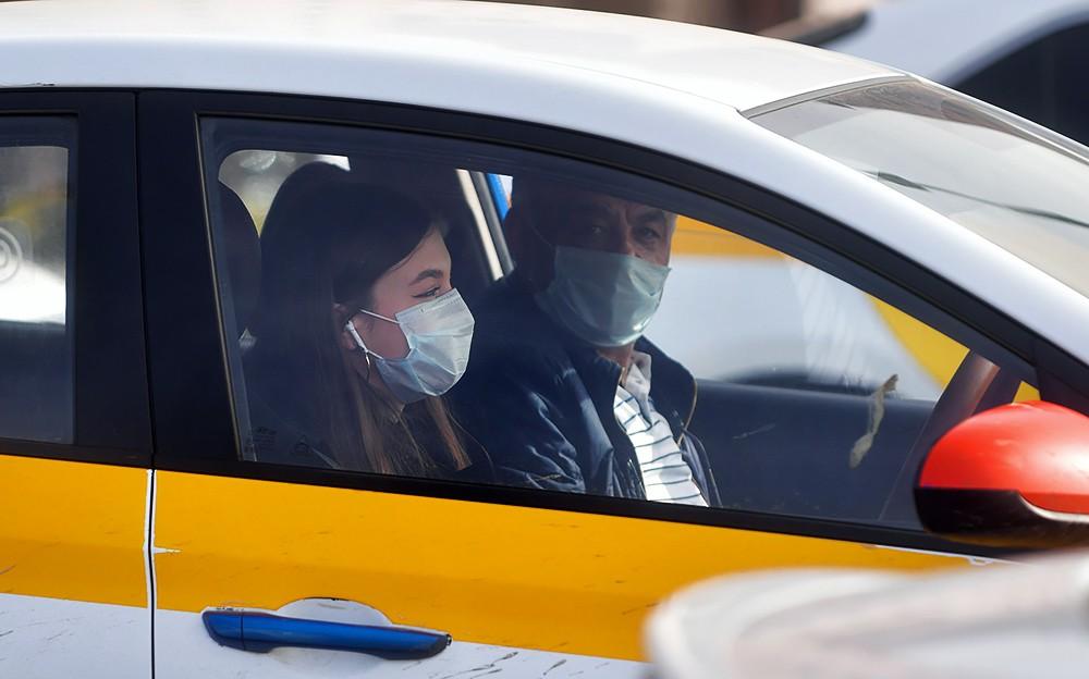 Люди в медицинских масках в такси