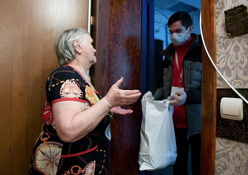 Волонтер передает доставленные на дом продукты пенсионерке