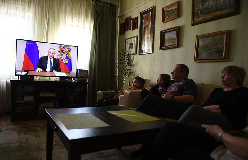 Жители Москвы смотрят у себя дома трансляцию обращения президента России Владимира Путина к гражданам