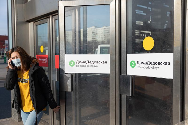 """Пассажир у входа на станцию метро со стикером на дверях """"ДомаДедовская"""""""