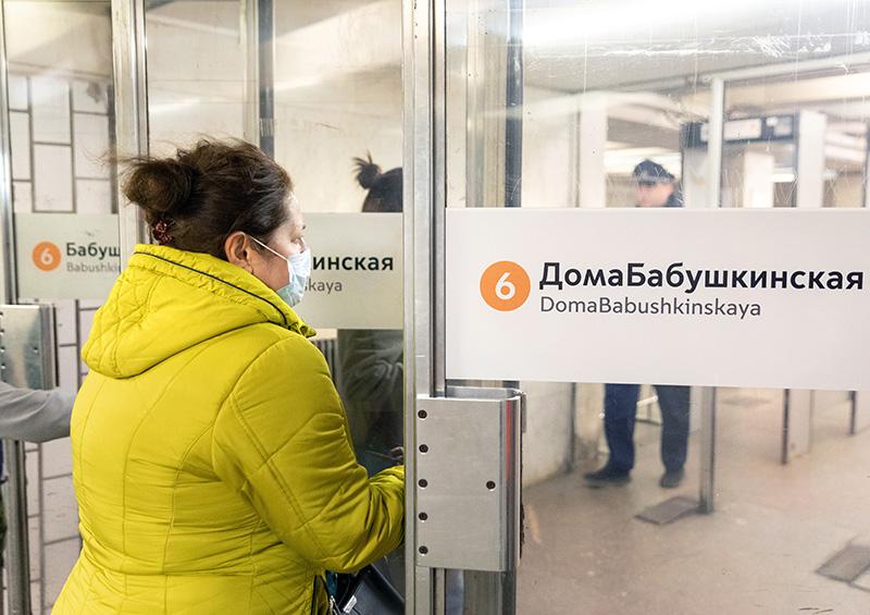 "Пассажир у входа на станцию метро со стикером на дверях ""ДомаБабушкинская"""