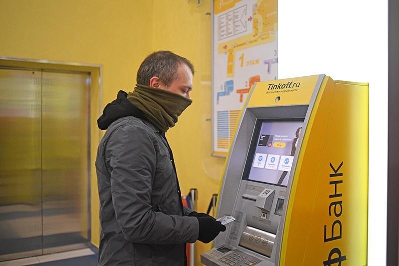 Мужчина пользуется банкоматом