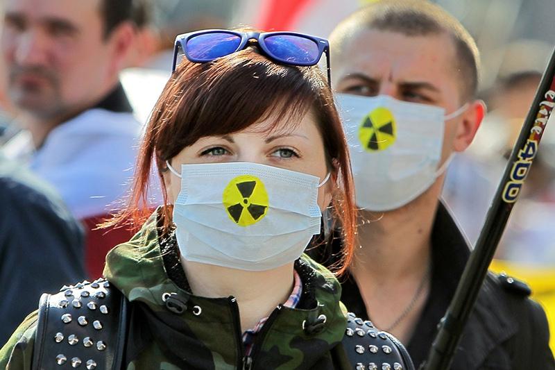 Люди в медицинских масках со знаком радиации