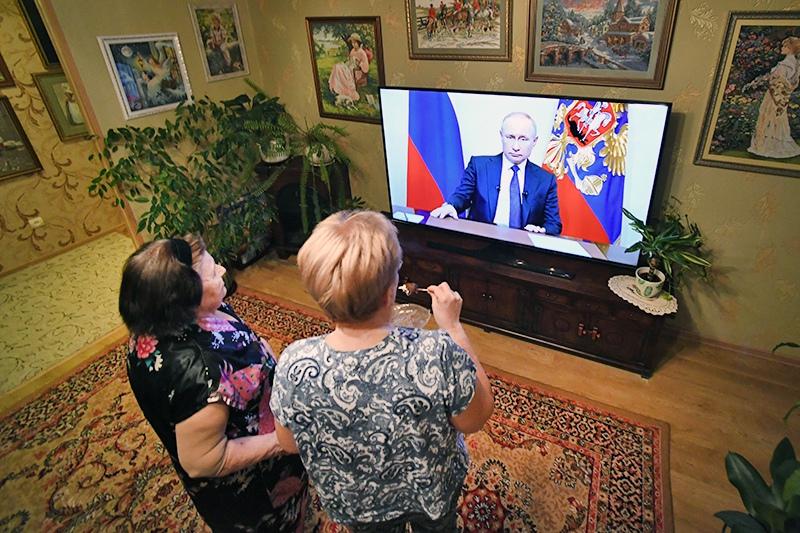 Люди смотрят обращение Владимира Путина по телевизору