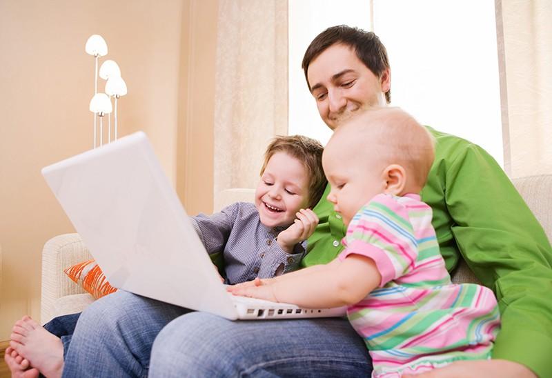 Мужчина с детьми за ноутбуком