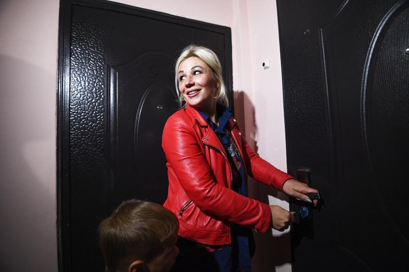 Девушка открывает дверь в квартиру нового дома