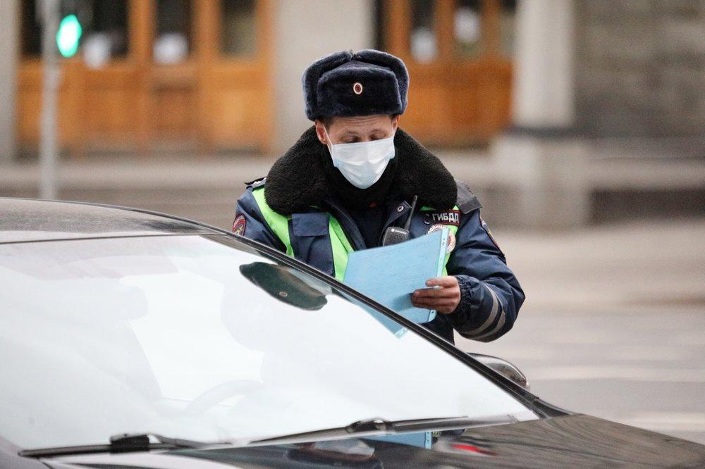 Инспектор ГИБДД проводит проверку документов у водителя в связи с эпидемией коронавируса