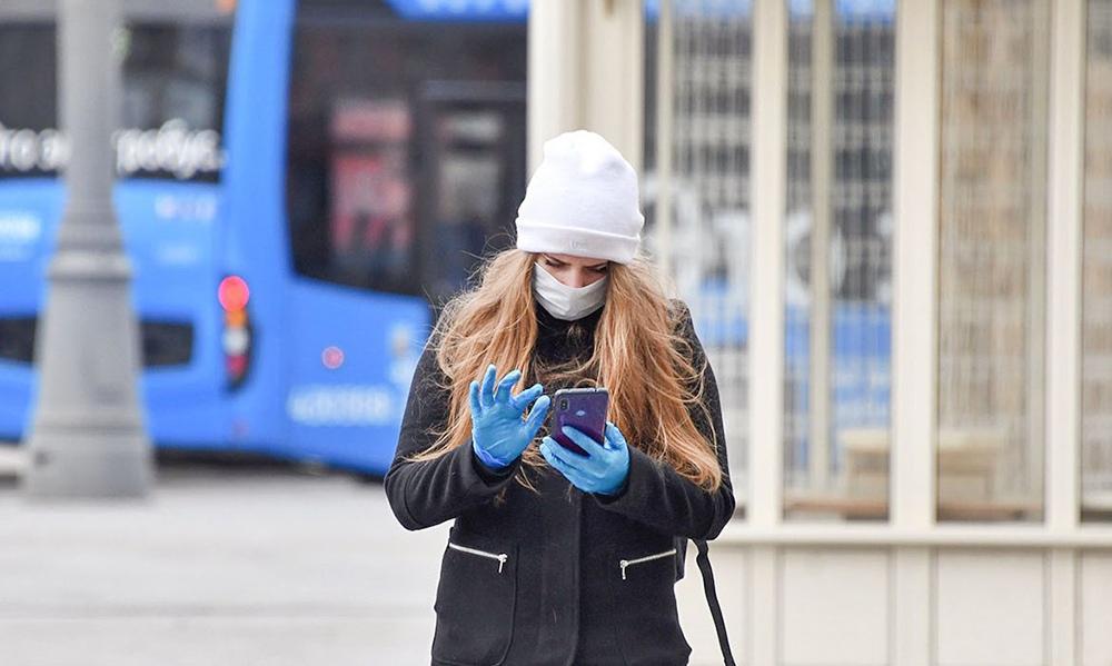 Девушка в медицинской маске и со смартфоном