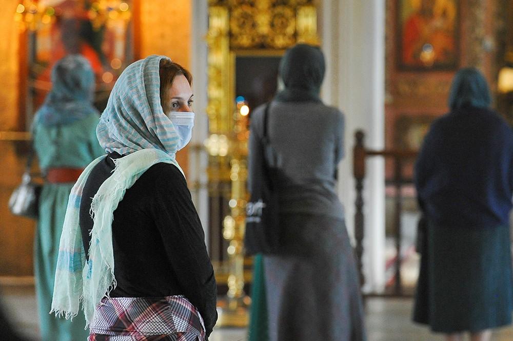 Девушка в медицинской маске в церкви