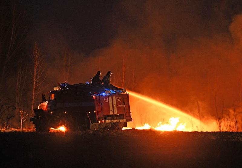 Сотрудники пожарной службы тушат полевой пожар