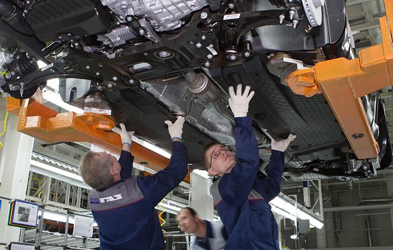 Рабочие на конвейере сборочного цеха автомобилей
