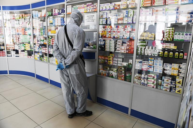 Человек в защитном костюме в аптеке