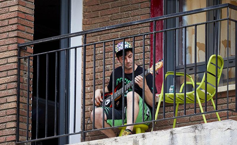 Мужчина играет на гитаре сидя на балконе
