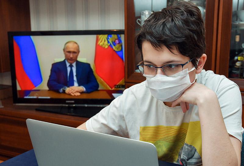Мальчик смотрит трансляцию обращения президента  Владимира Путина