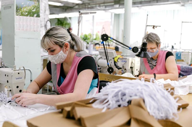Сотрудницы изготавливают защитные маски в швейном цехе