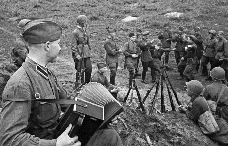Советские солдаты поют песни и танцуют в перерыве между боями