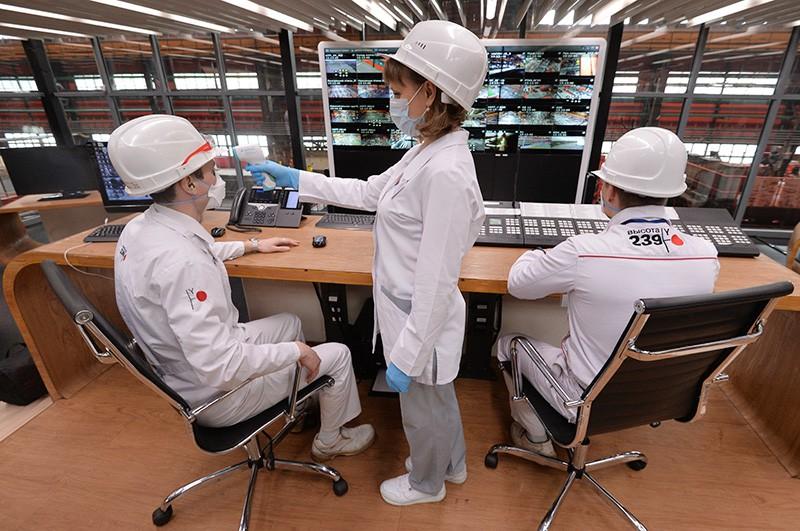 Медицинский работник измеряет температуру у сотрудников предприятия