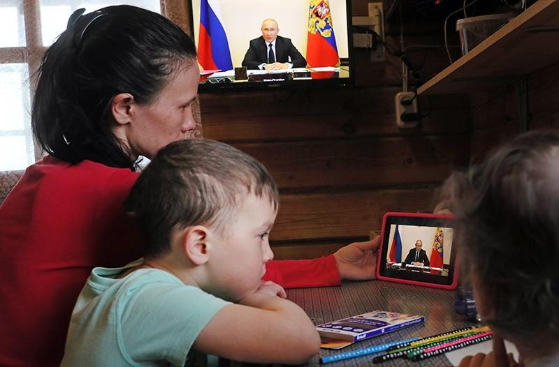 Женщина с детьми смотрит трансляцию совещания Владимира Путина