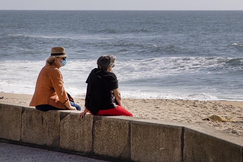 Люди в медицинских масках на пляже