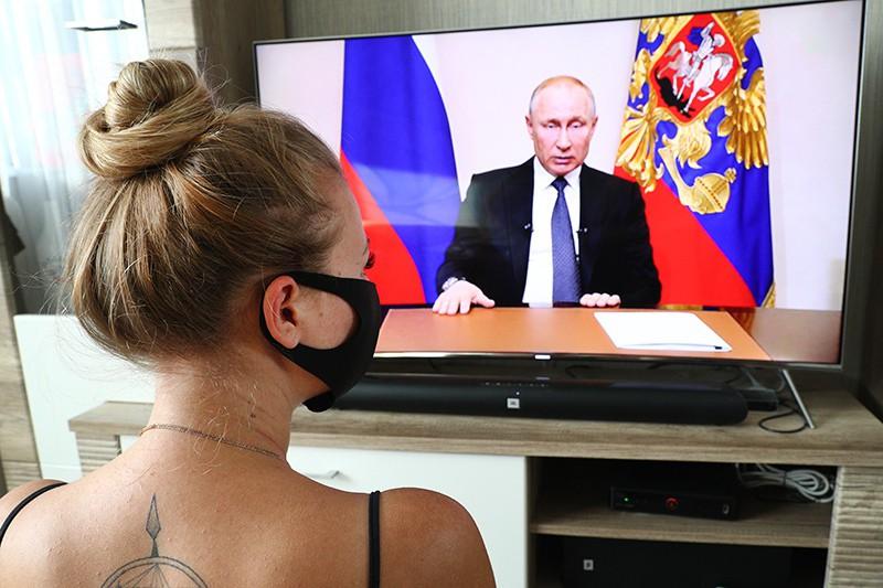 Девушка смотрит обращение Владимира Путина по телевизору