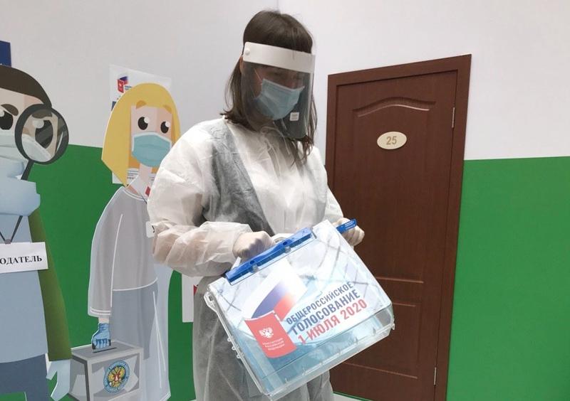 Девушка в защитном костюме члена участковой избирательной комиссии для проведения голосования