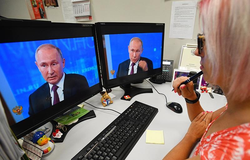 Девушка смотрит трансляцию с Владимиром Путиным