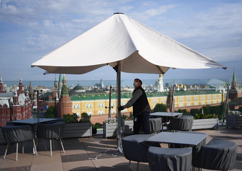 Рабочий устанавливает зонтики на летней веранде ресторана
