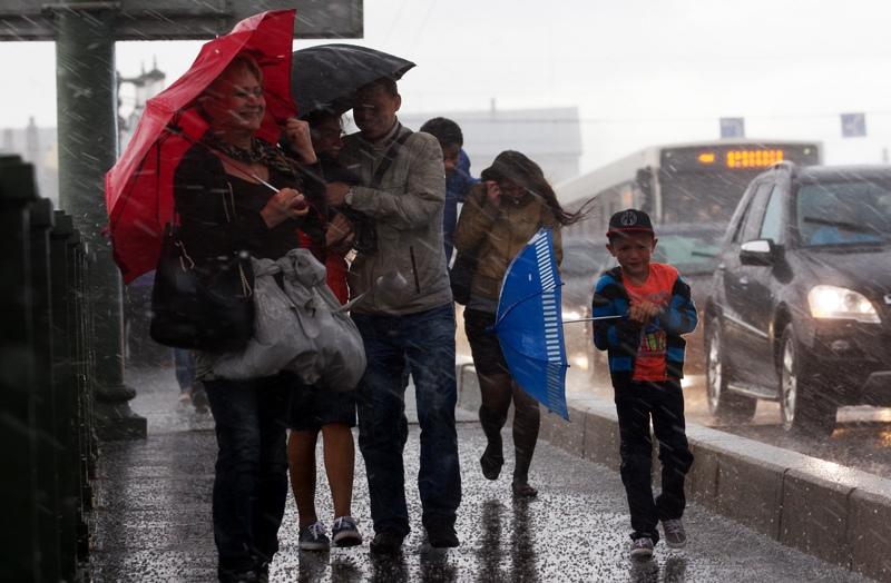 Жители Санкт-Петербурга на одной из улиц города во время сильного дождя