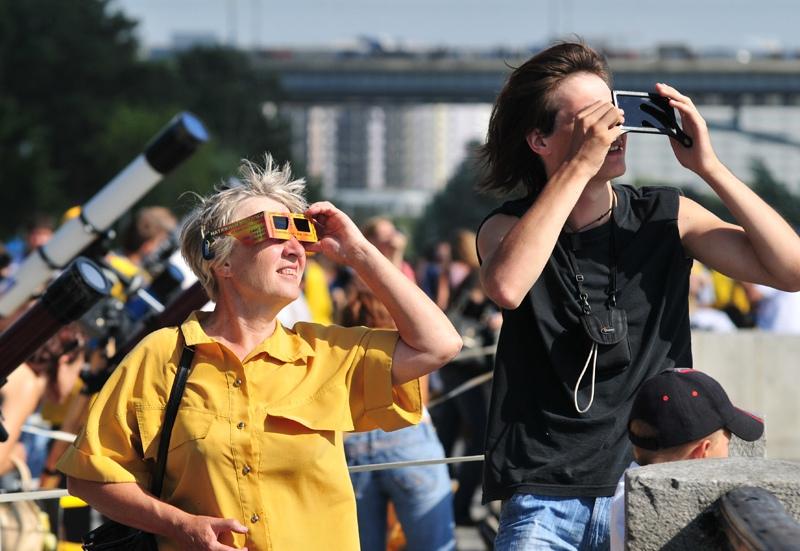 Люди наблюдают за затмением Солнца