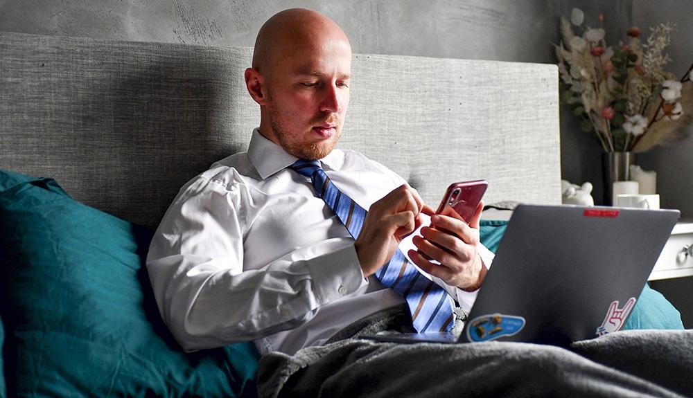 Мужчина со смартфоном за ноутбуком