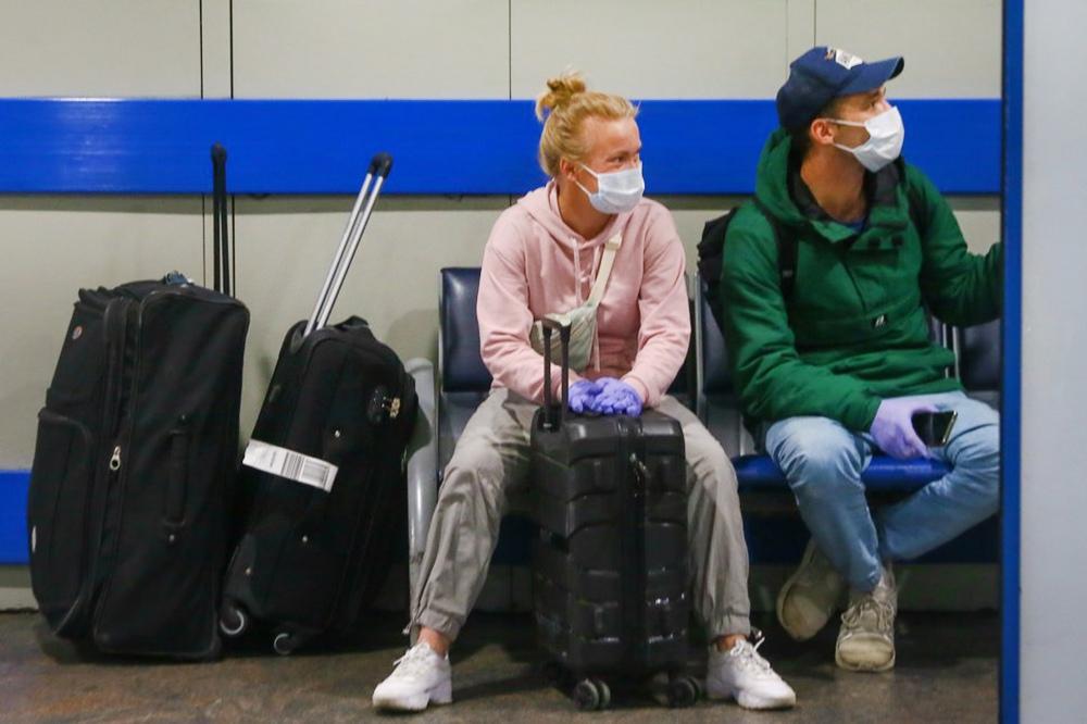 Люди в медицинских масках в аэропорту
