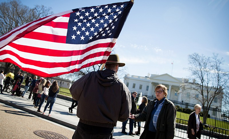 Мужчина с флагом США у Белого дома