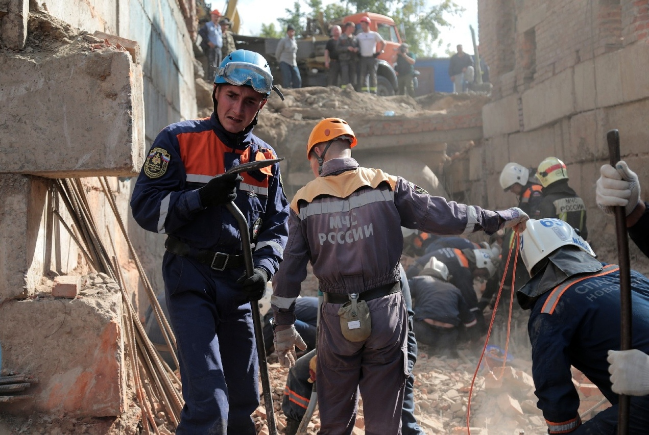 Сотрудники МЧС разбирают перекрытия, рухнувшие в строящемся здании