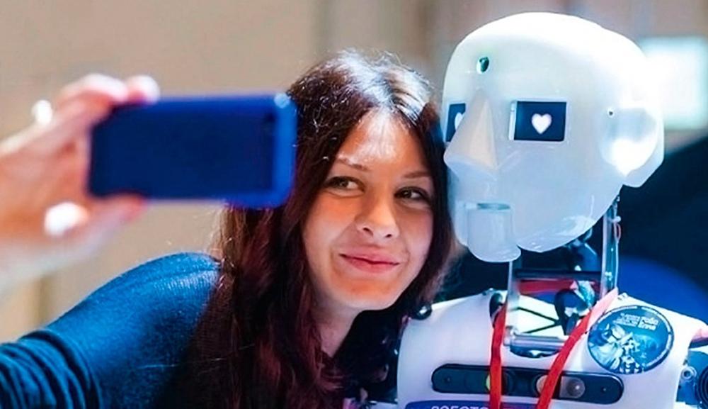 Девушка делает селфи с роботом