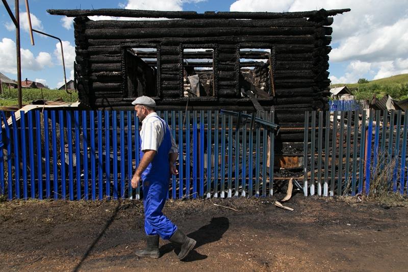 Мужчина у сгоревшего частного дома