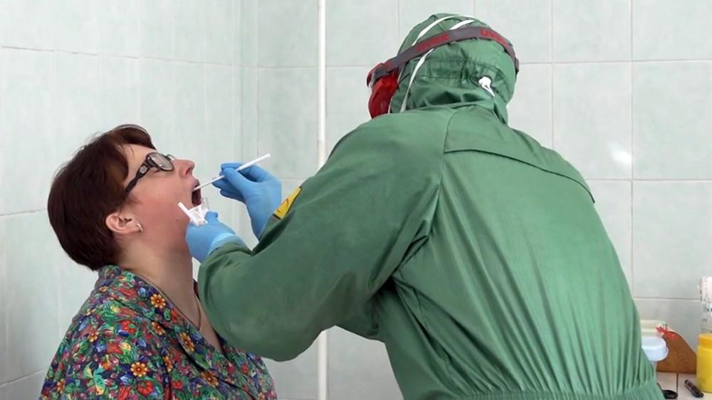Врачи в защитных костюмах осматривают пациентов